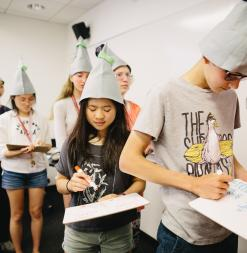 Wearing conical hats and writing on personal whiteboards, participants standing in a line participate in a mathematics challenge.