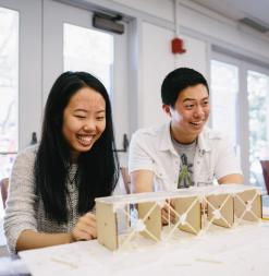 Participants laugh as they look at their designed bridge during a civil engineering course.