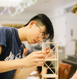 Engineering student builds a small tower out of wooden pieces.