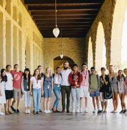 A group of participants stands in Stanford's famous Main Quad arches.