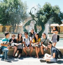 Participants sit beside a Stanford fountain.